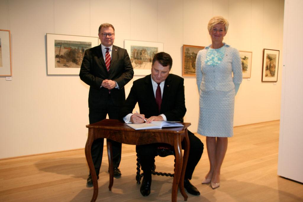 Der Lettische Staatspräsident beim Eintrag in das Besucherbuch des Museums