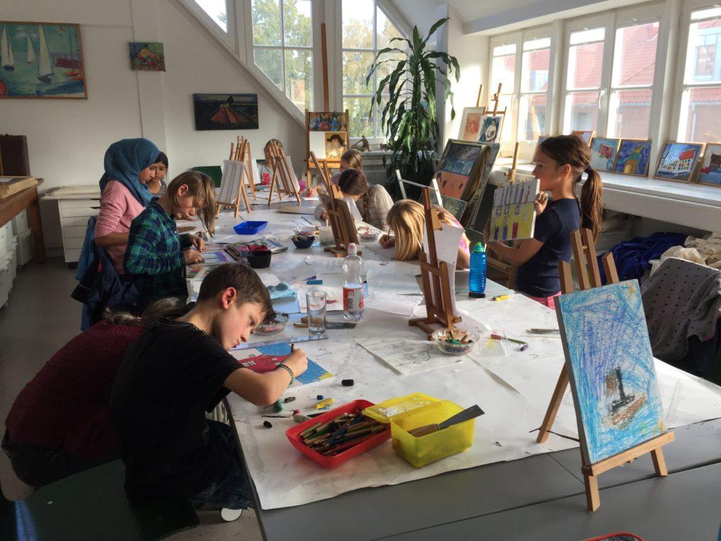Konzentriert bemalen die Kinder ihre Holzplatten mit Ölkreide.