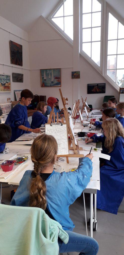 Die Kinder malen ihre Skizzen mit Acrylfarbe auf die Leinwand.